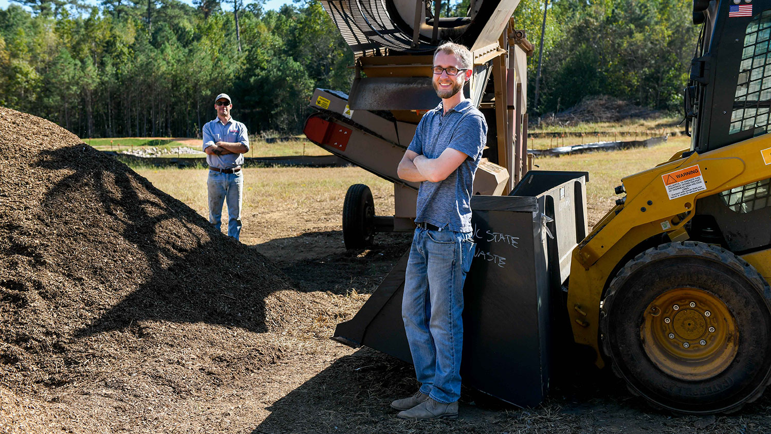 two men standing near compost at NC State's compost facility