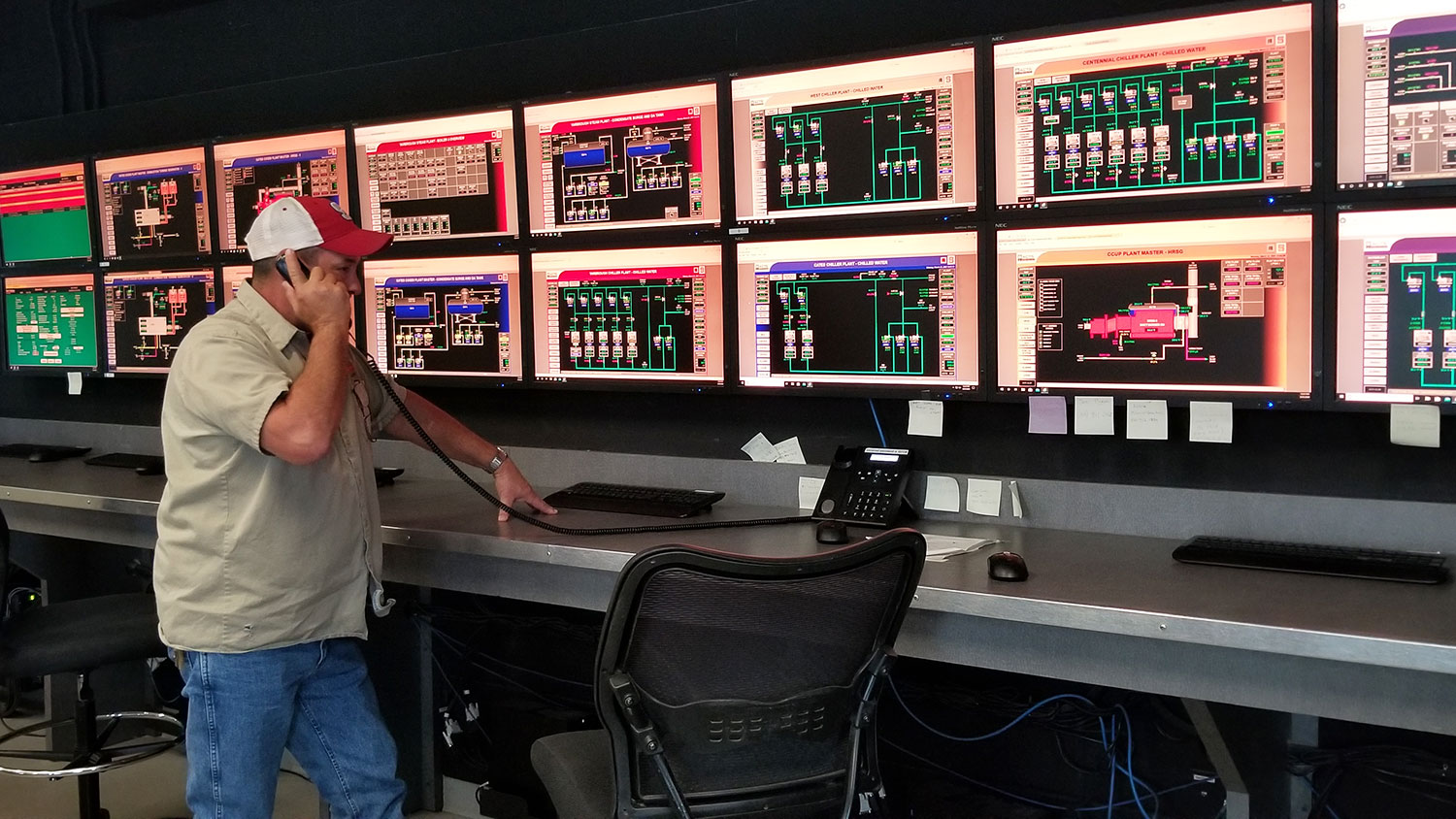 A central utility plant operator on the phone in a control room