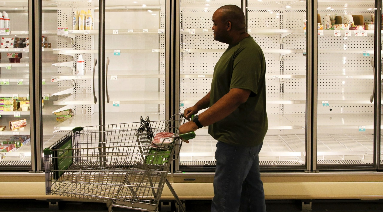 Supermarket shopper pushing cart past empty refrigerator cases