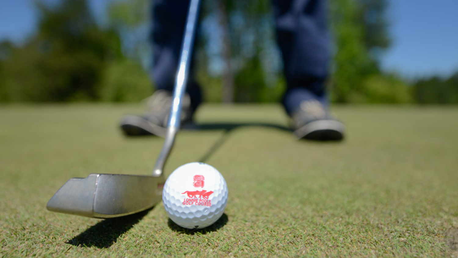 close up of a ball with a golfer about to put.