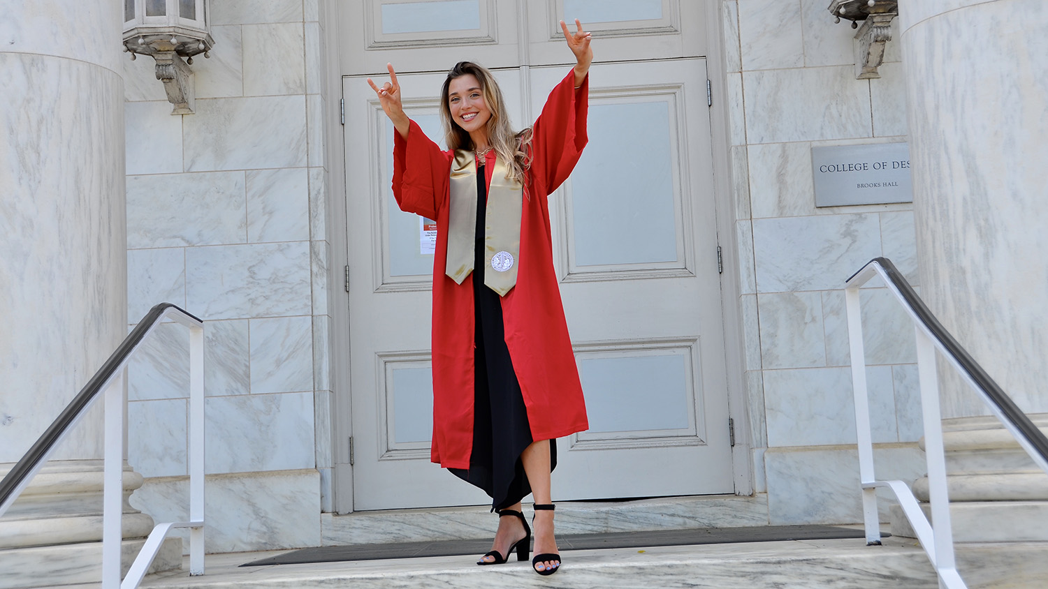 On the stone front steps of the College of Design building, Katherine Hord poses with wolf hands in her red graduation robes.