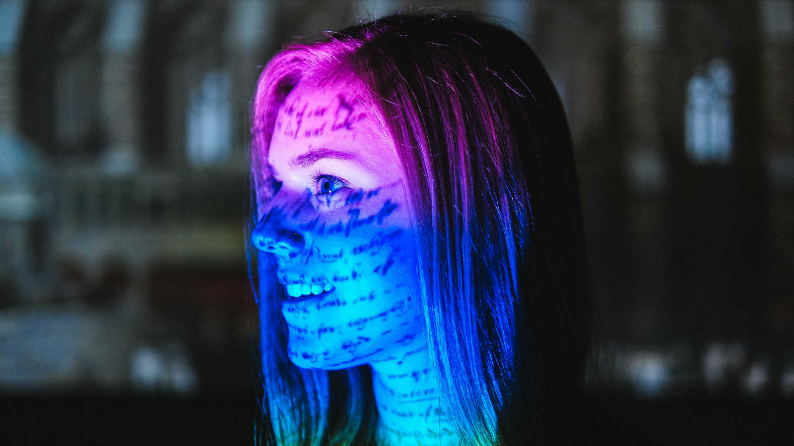 A young woman looks at a projected, colorful image of caligraphy.