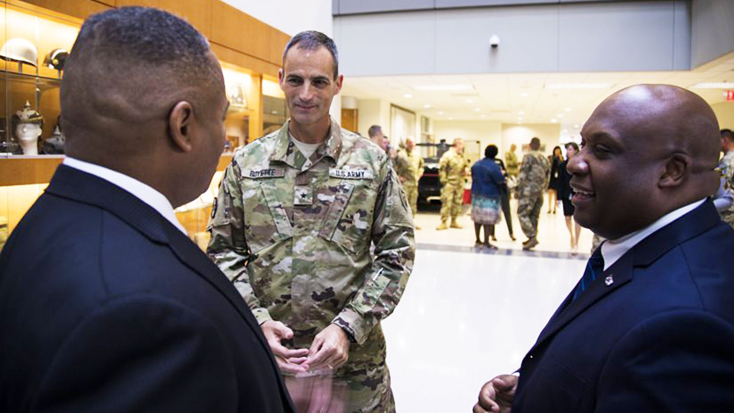 man in National Guard uniform talking with two other men