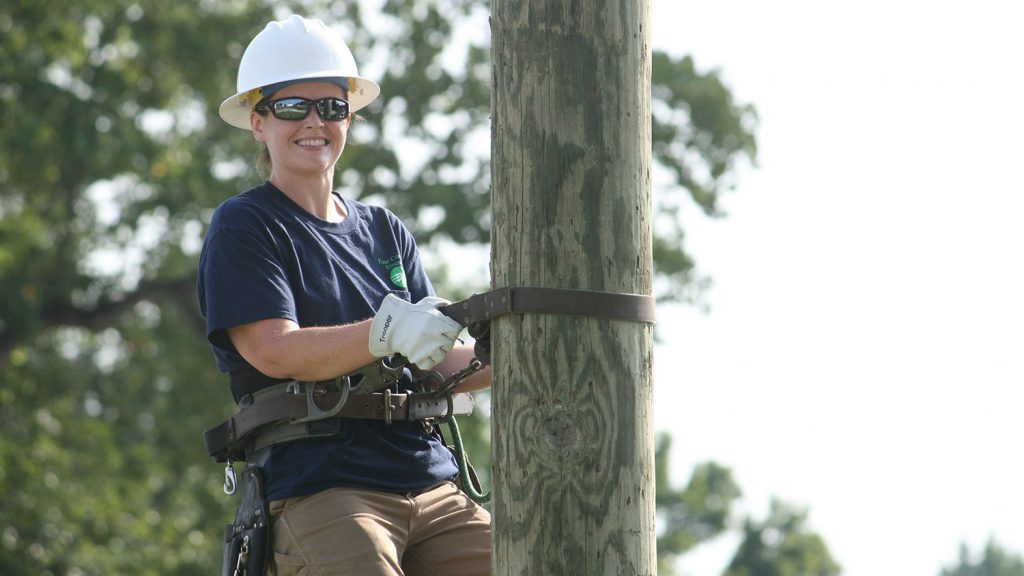woman in hard hat on electrical pole