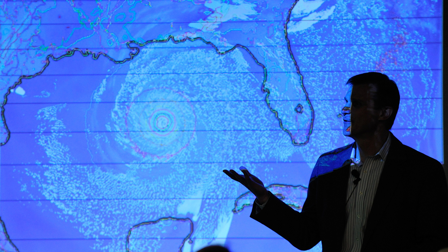 A person silhouetted against a weather map displaying a hurricane