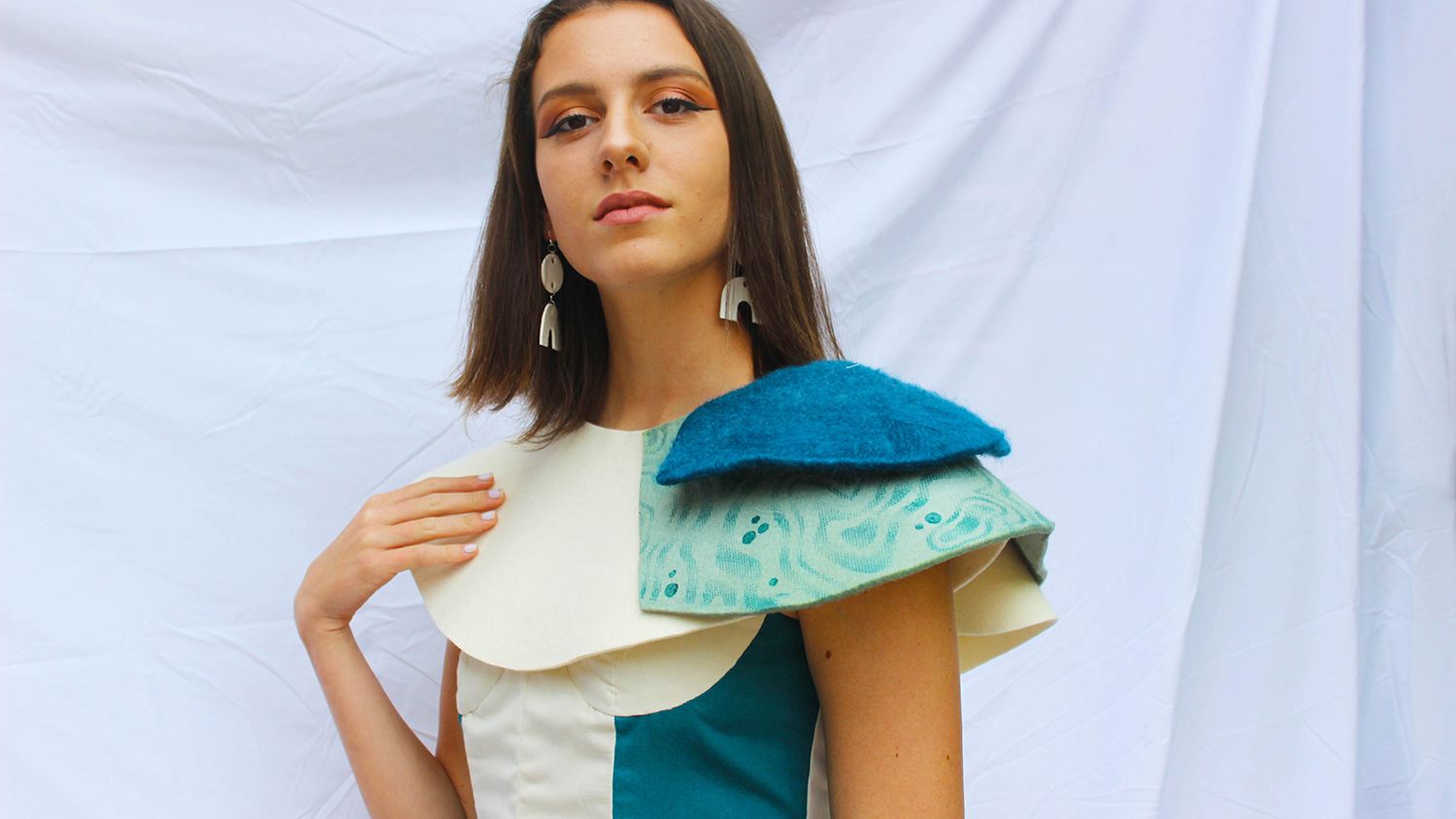 A student models a colorful blue and white garment created for Art2Wear.