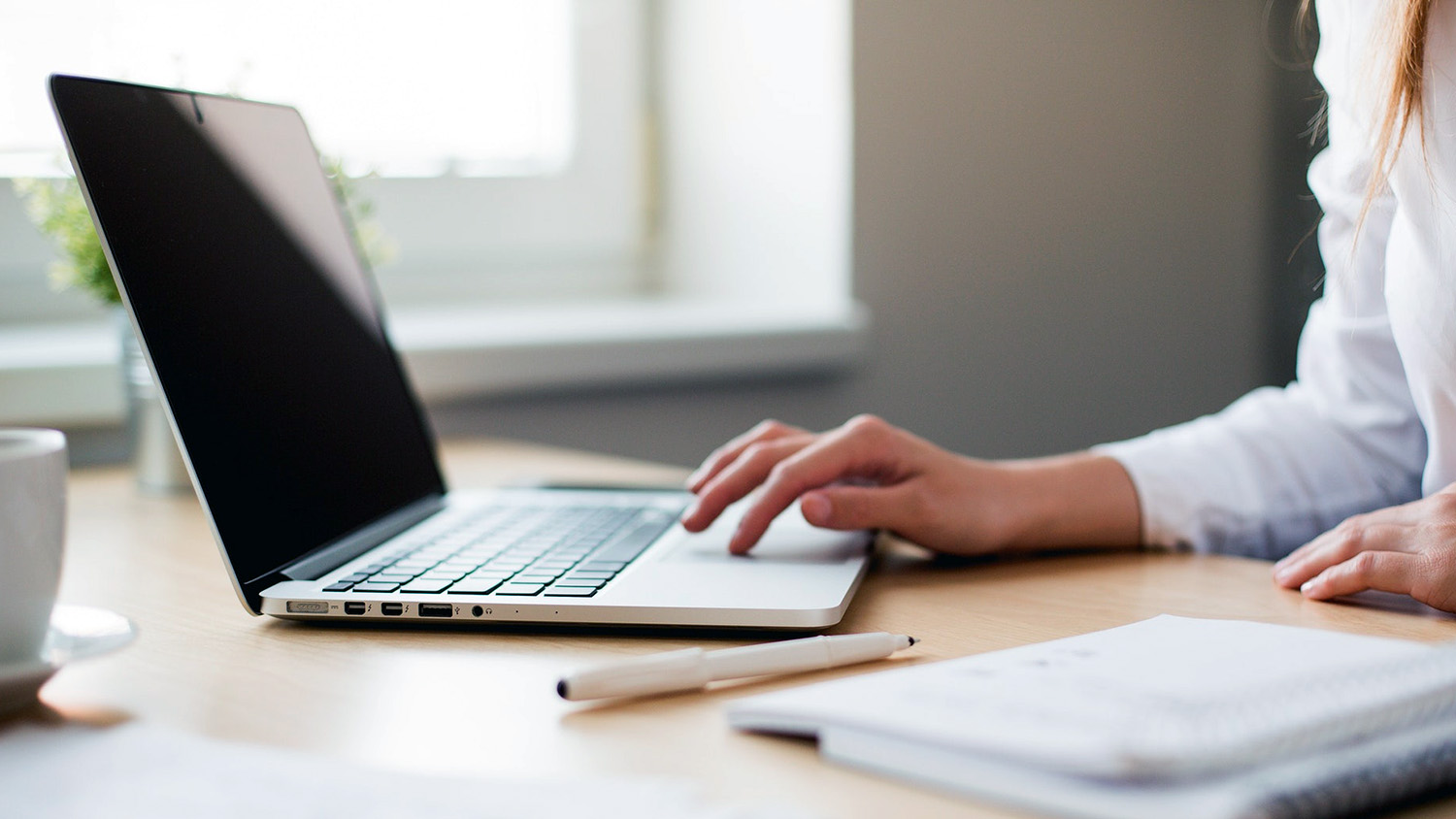 woman's hands typing at laptop on desk