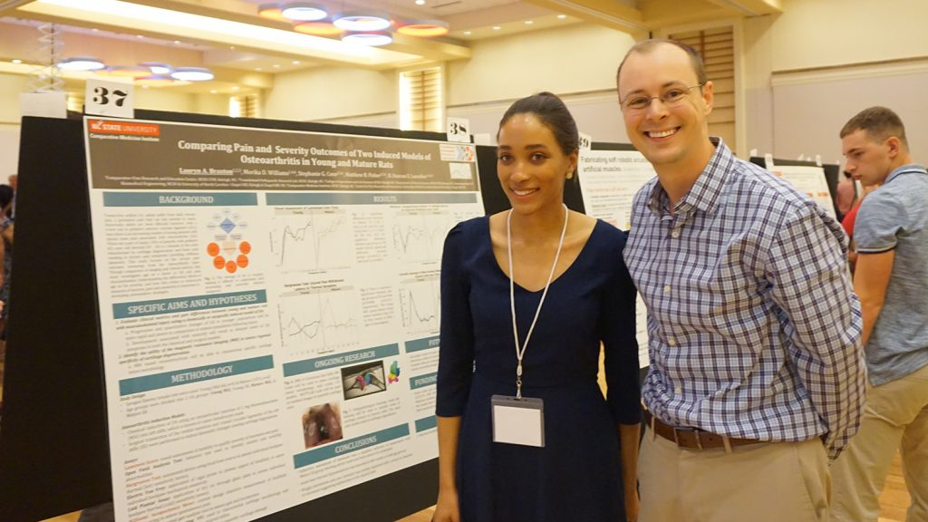 Student Lauryn Braxton and Professor Matt Fisher stand next to Braxton's research poster.