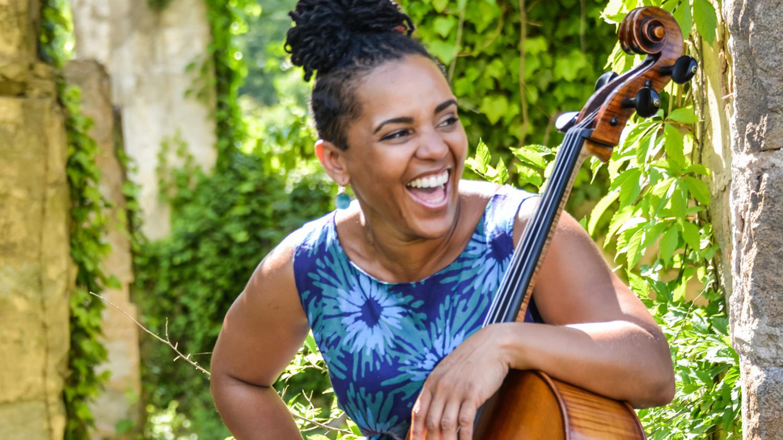 A cellist smiles in a garden.