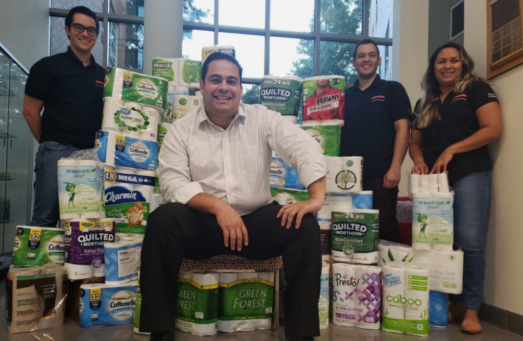 Ronalds Gonzalez sits on a make-shift chair made out of toilet paper packages while posing with three students.