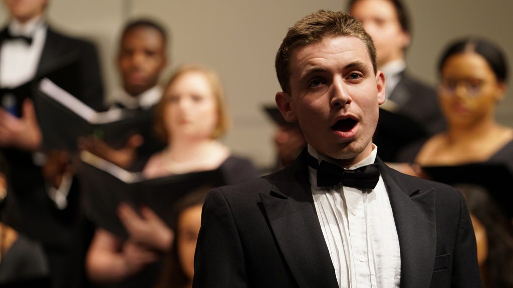 A young man sings on stage with a choir behind him.