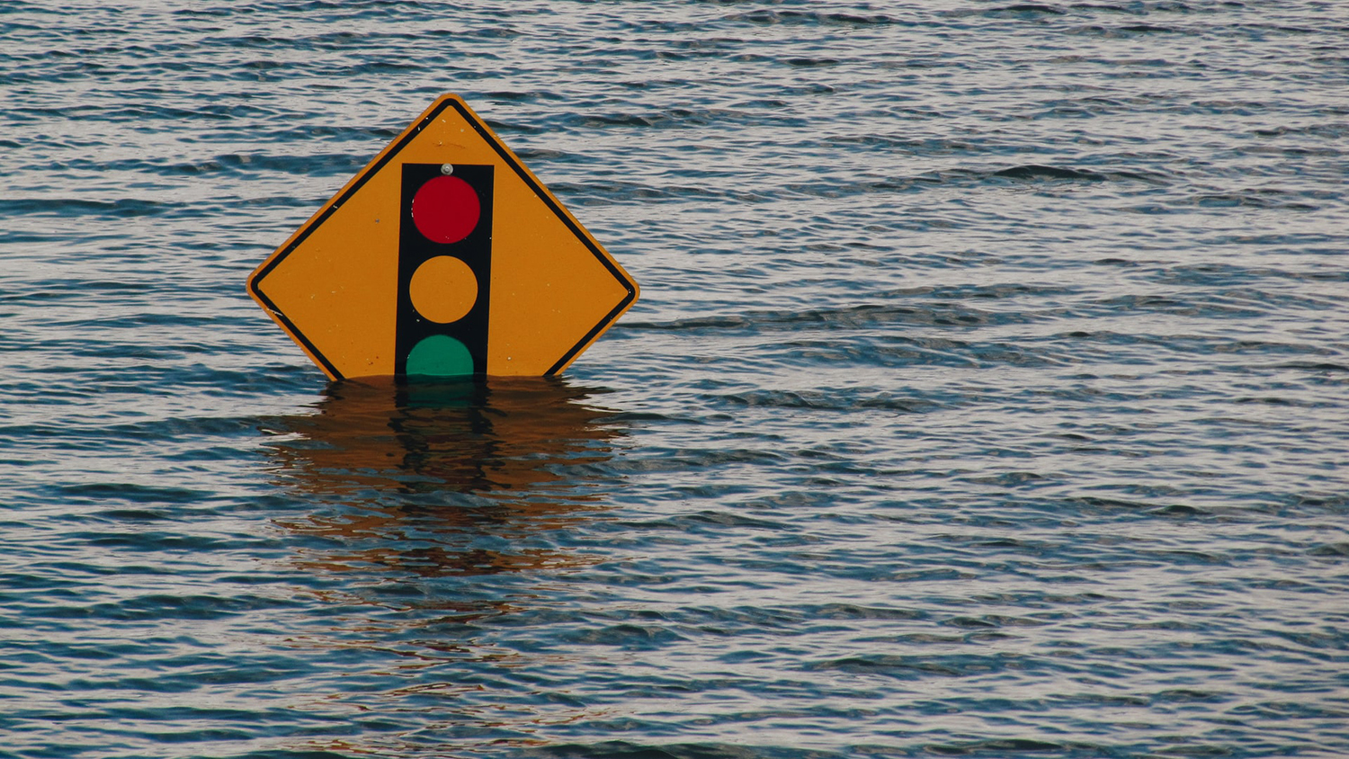 traffic sign almost completely submerged by flood waters
