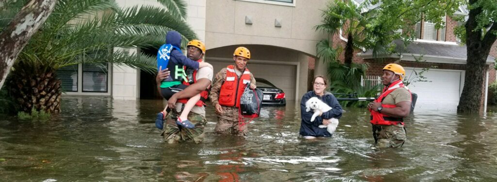 military personnel help family evacuate in waist-deep flood waters