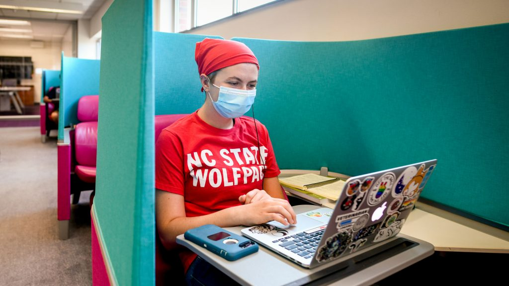 A student wearing a face mask and an NC State t-shirt studies in a blue chair in the Hill Library.