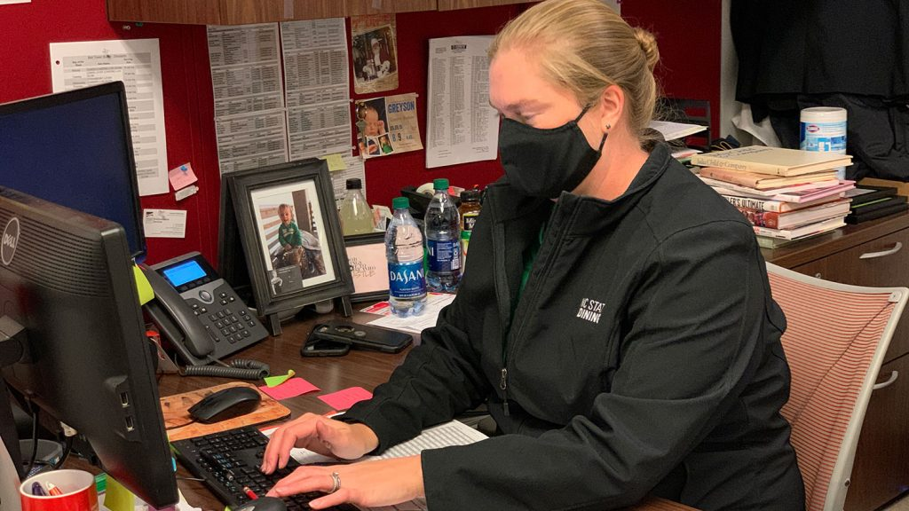 woman at desk wearing a mask