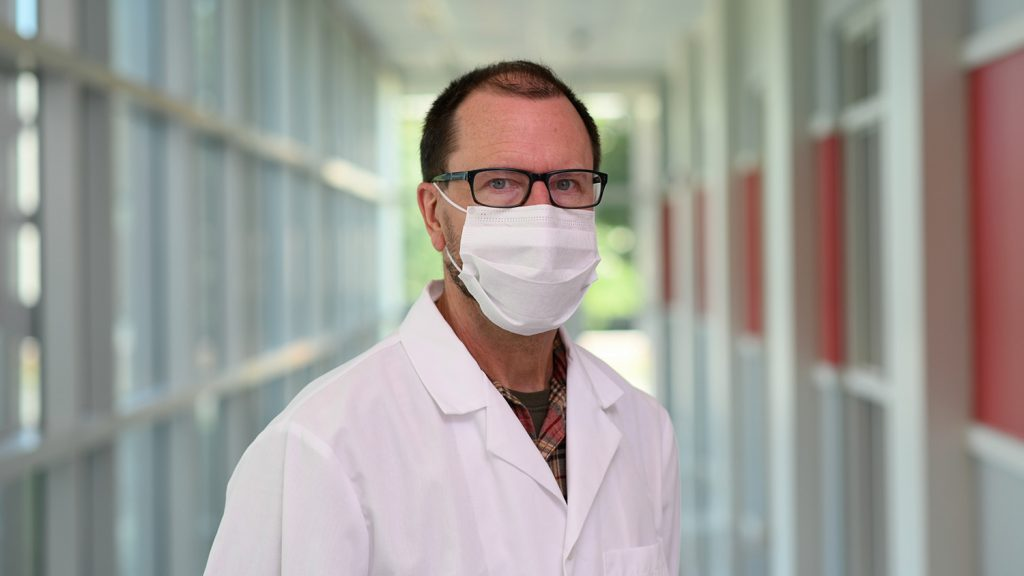 A man wears a surgical mask in a hallway.
