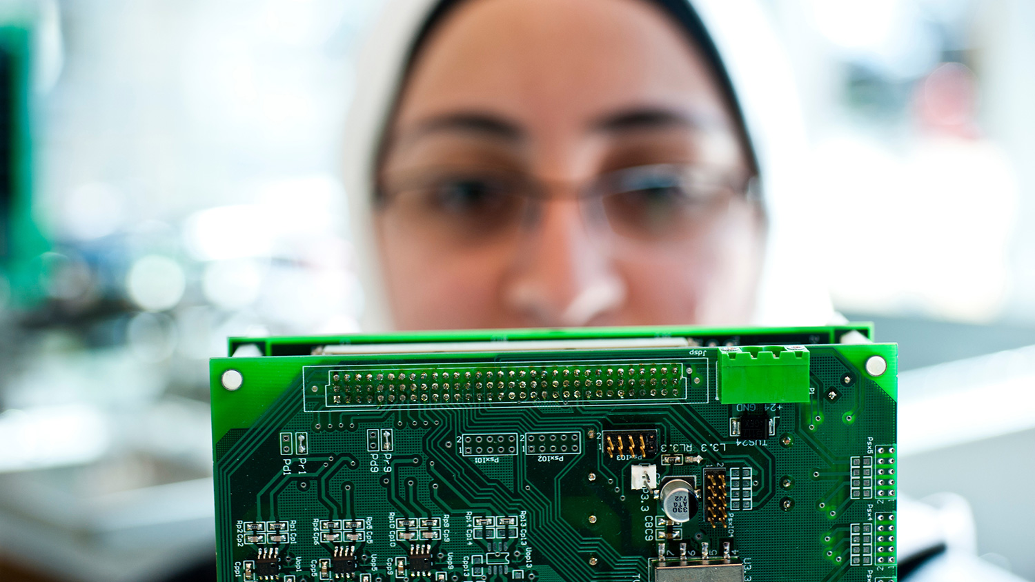 A woman holds a circuit board.