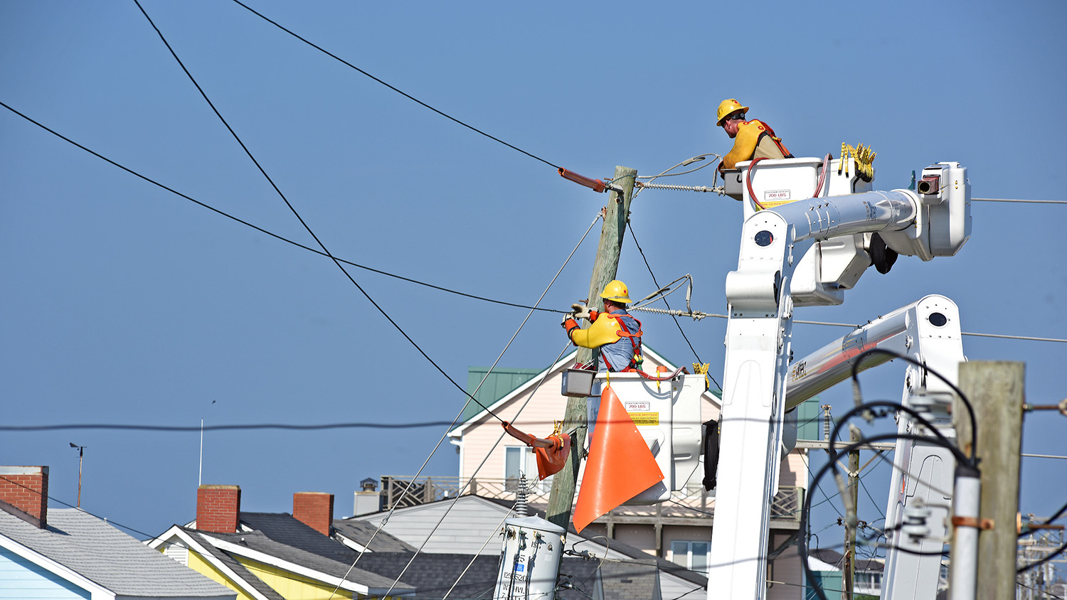 Linemen work on electric lines and poles at Atlantic Beach, NC.