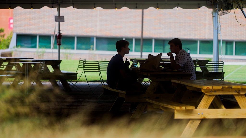 Students eat lunch together at a picnic table under a tent on Centennial Campus's Oval.