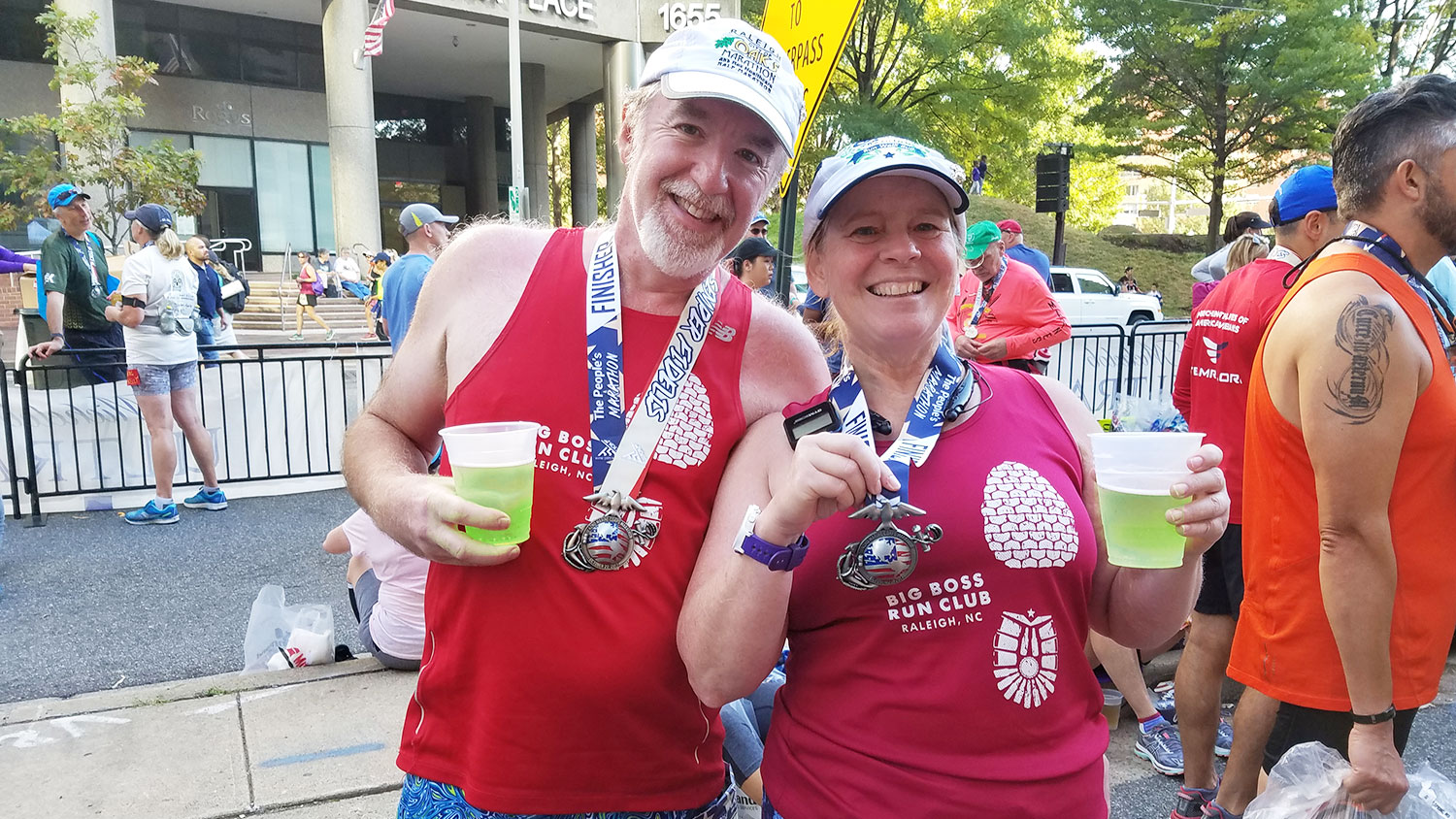 man and woman wearing marathon medals after a race