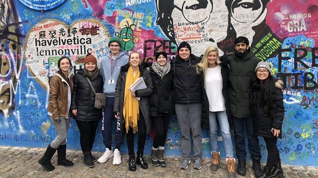 Students pose in front of mural of John Lennon in Prague.
