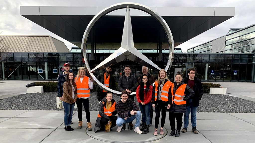 Students pose with a giant Mercedes Benz logo outside the plant in Germany.