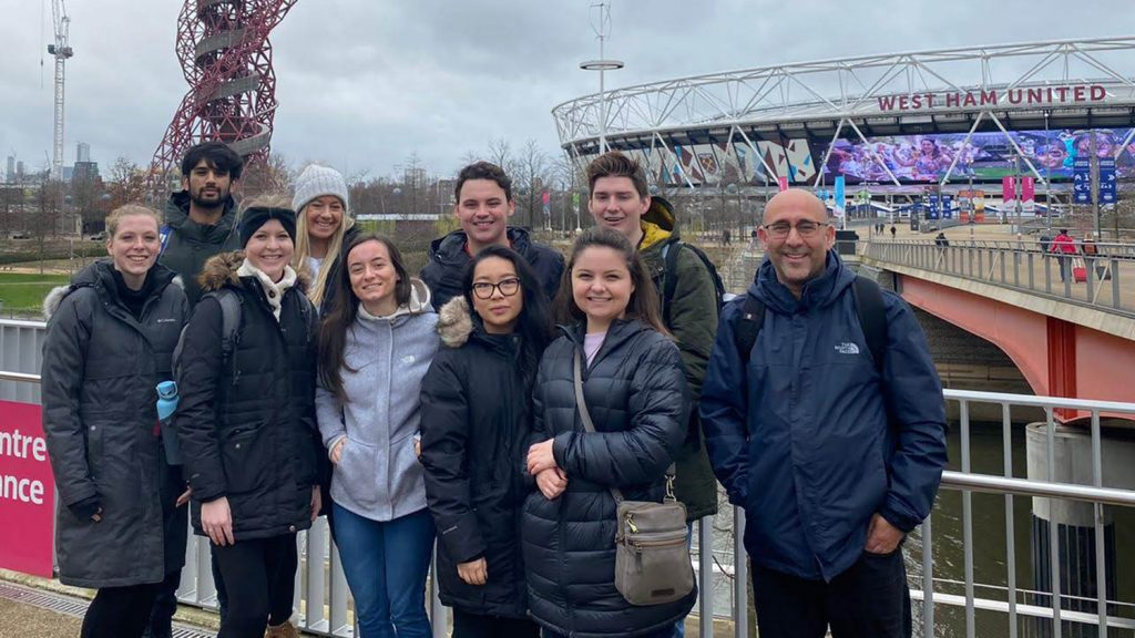 Professor and students pose in front of London Stadium.