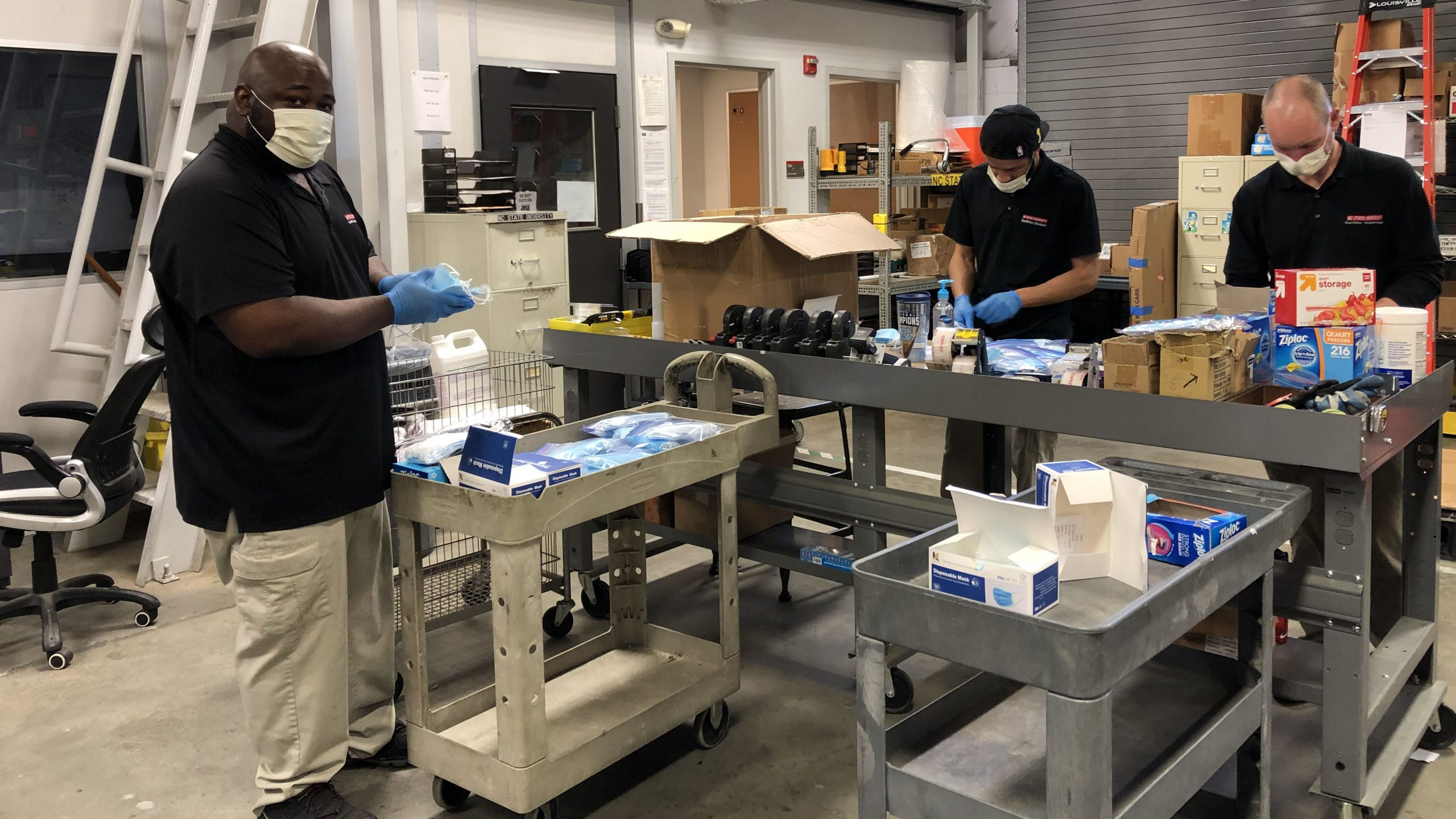 In the campus warehouse, three Facilities employees prepare materials in for workers' welcome kits.