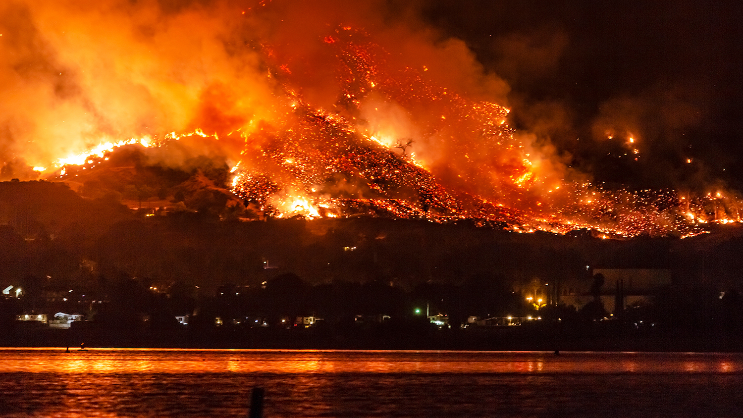 A wildfire burns near a lake in California.