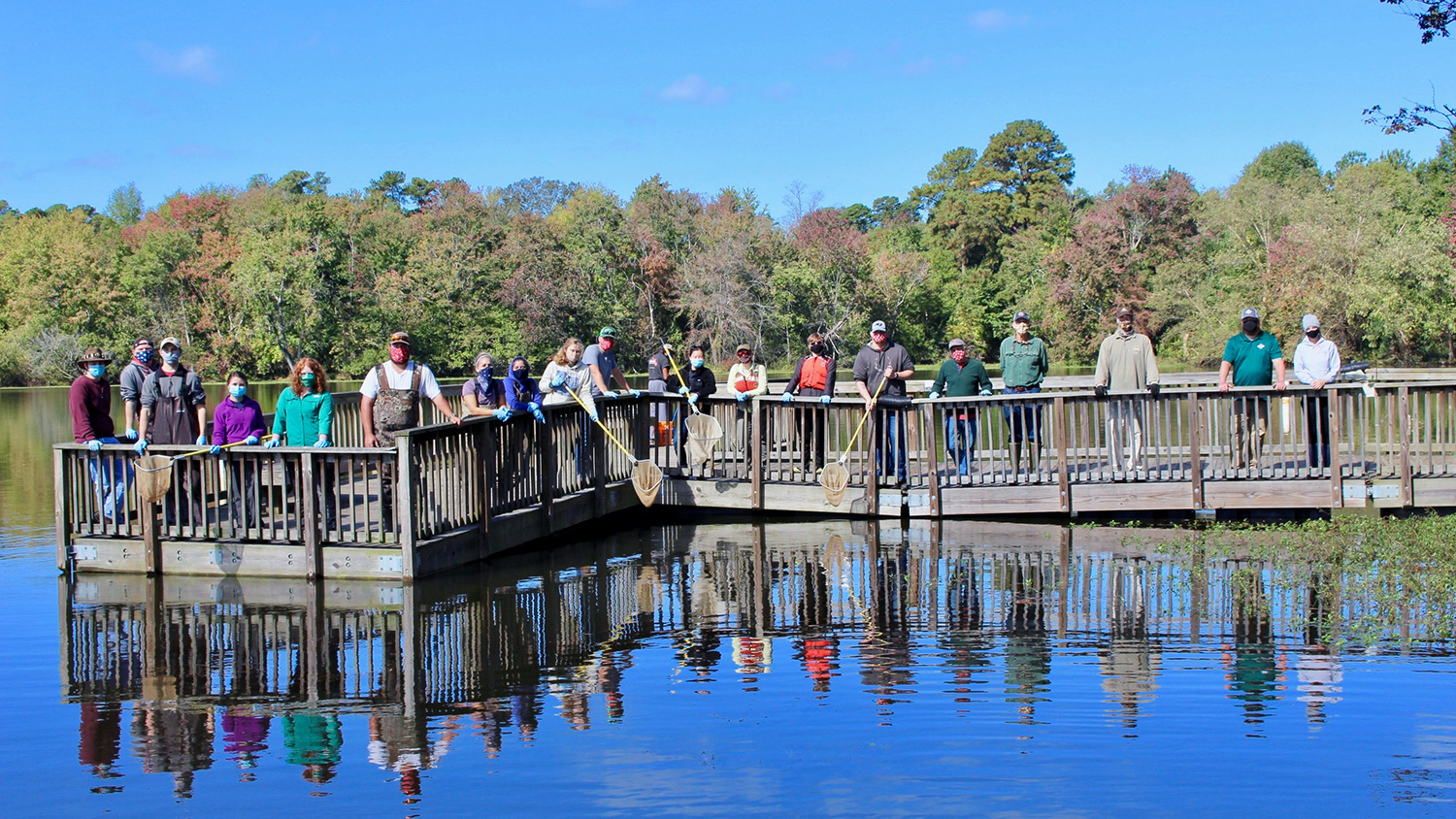 At Lake Raleigh, students stand on a dock after a day of collecting data about fish populations.