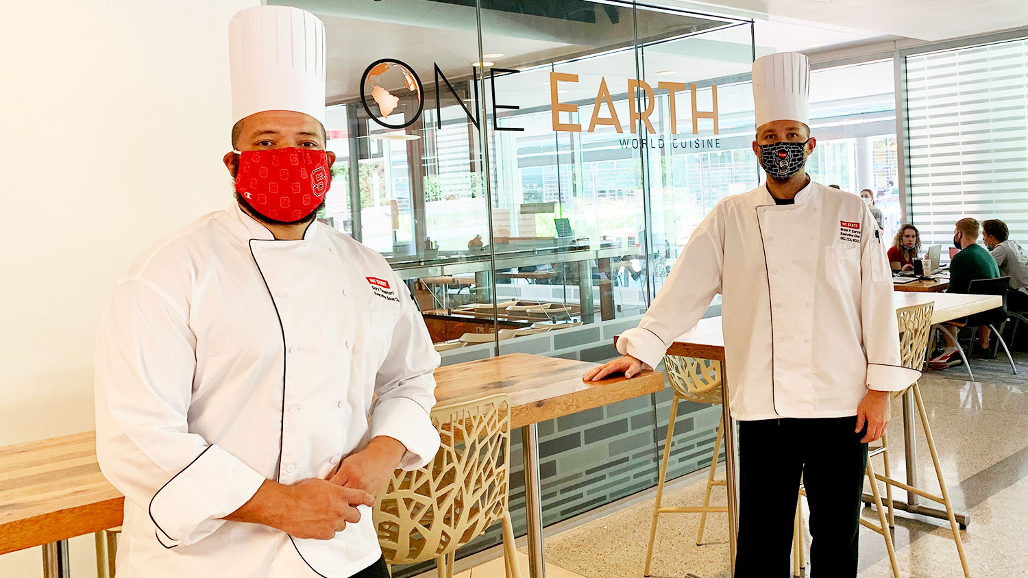 Two chefs from University Dining pose in their face masks.