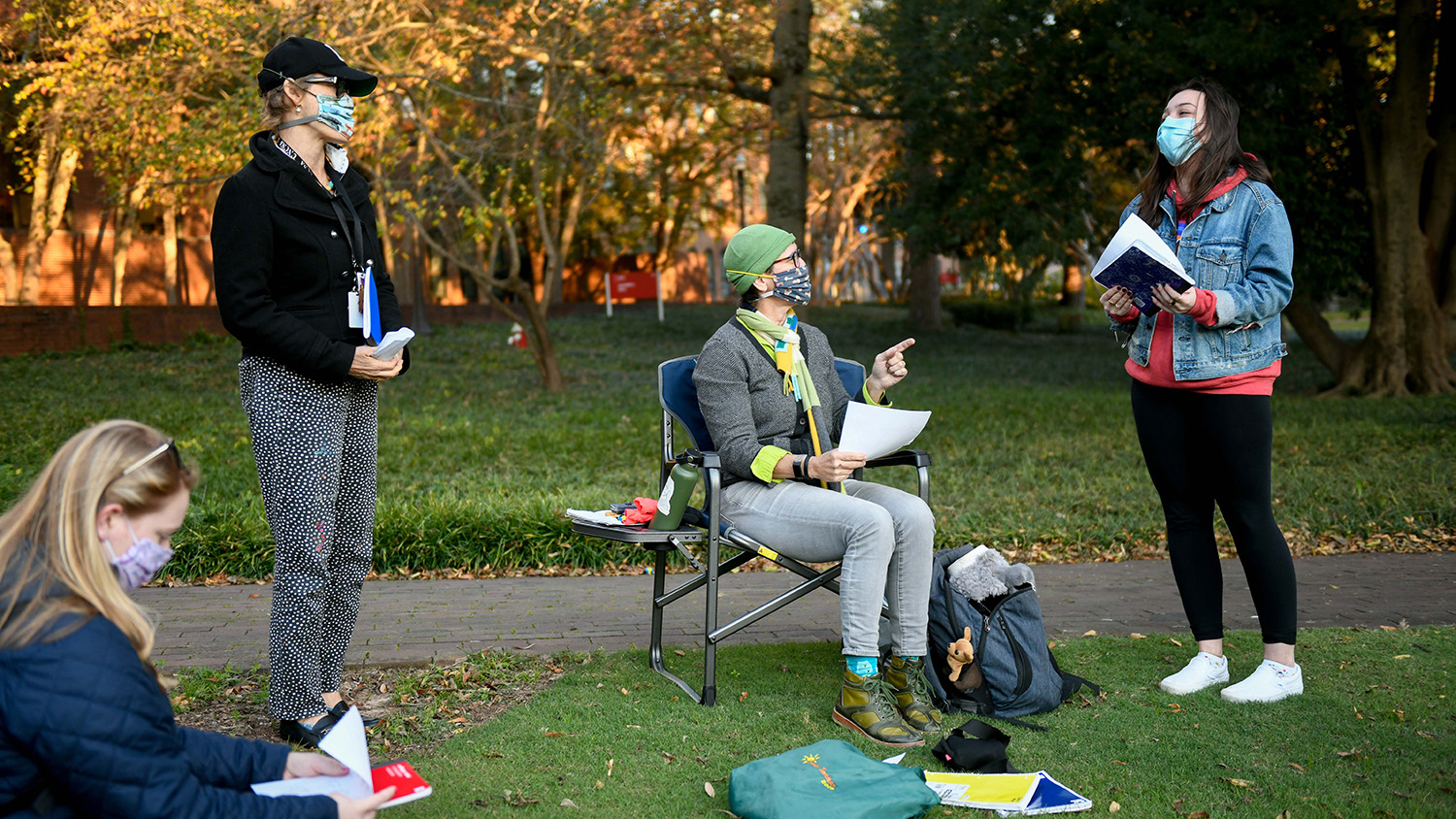 Valerie Faulkner talks with students at a socially distanced outdoor journal exchange