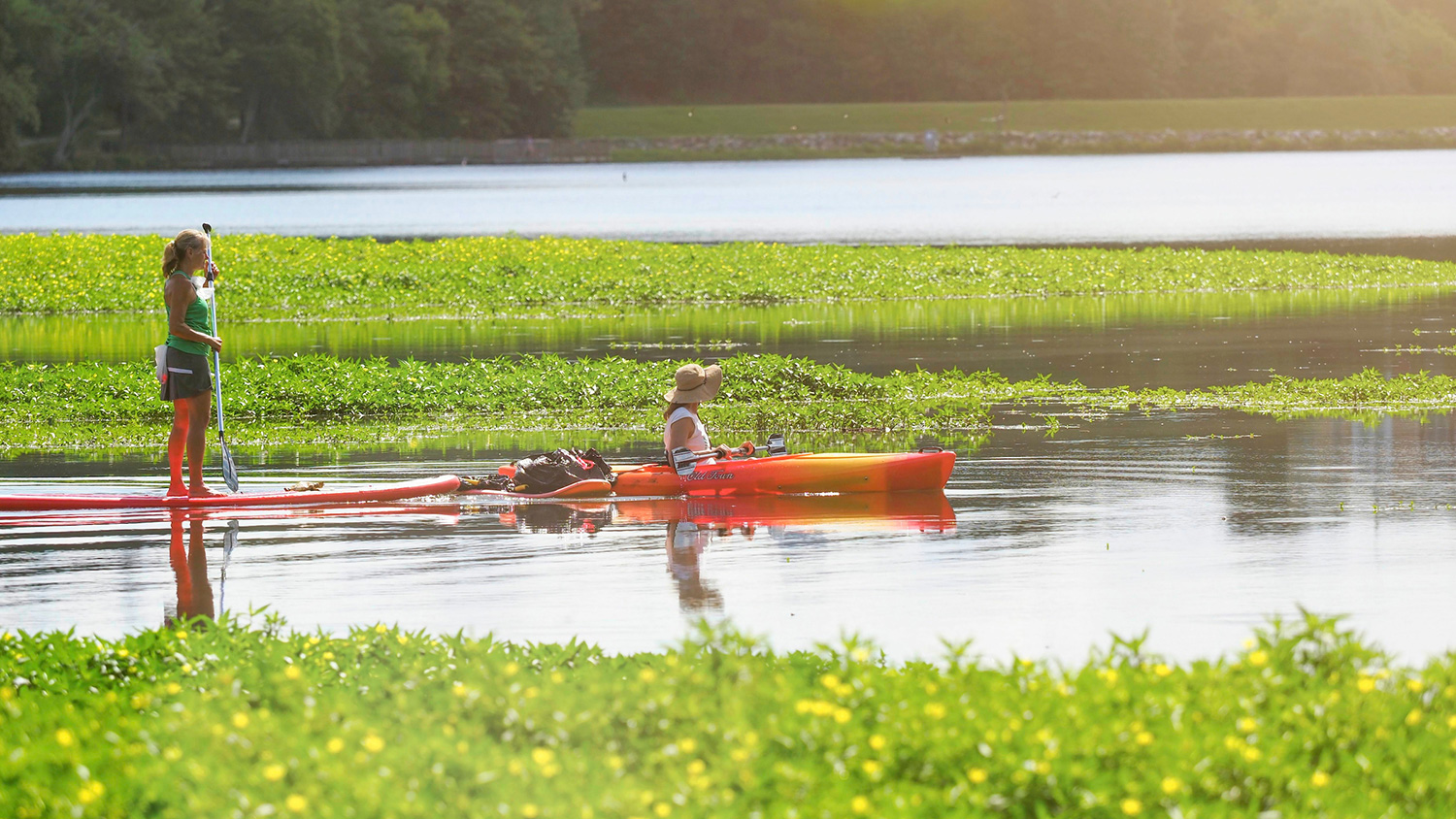 Two women paddling kayaks on Lake Raleigh.