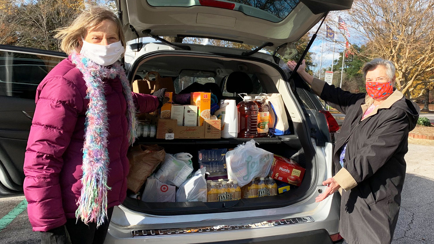 two women standing next to car packed with food donations