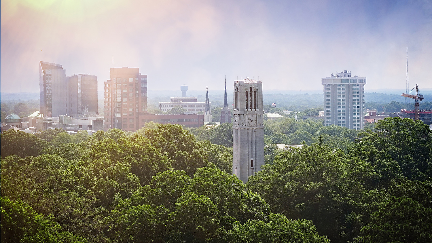 The NC State belltower sits in front of the city of Raleigh skyline as seen from a DH Hill library window.