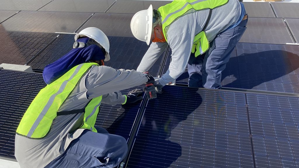 Workers place solar panel in place.