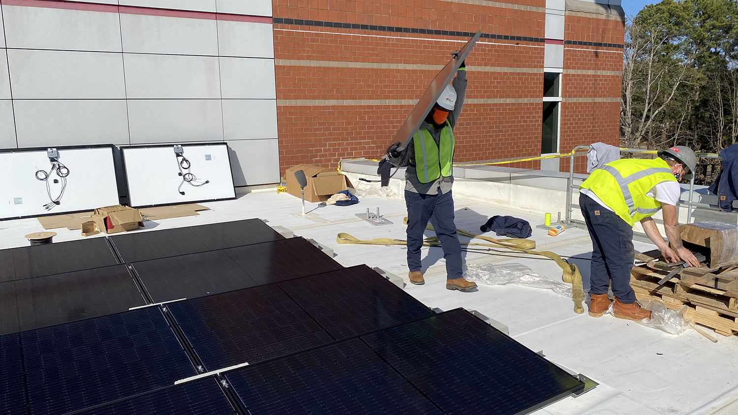 Worker carries solar panel on the roof of the Murphy Center.