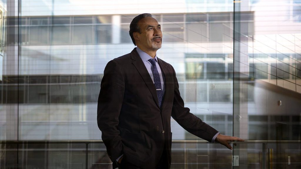 A photo of Phil Freelon in front of a glass building