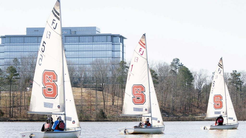 Three sailboats with the NC State block S logo on their sails on a lake