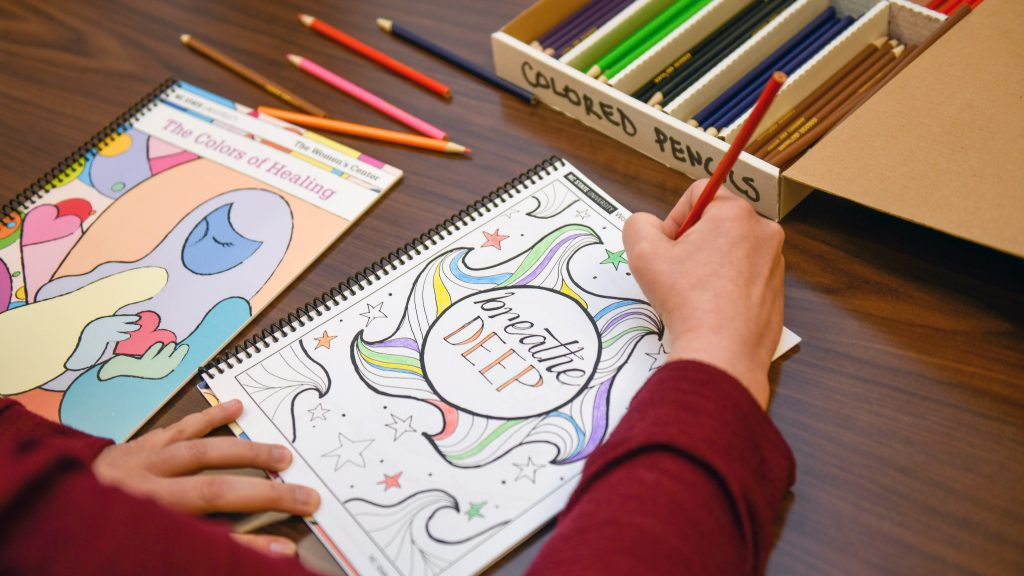 "A hand colors in a coloring book page that reads ""Breathe Deep."""