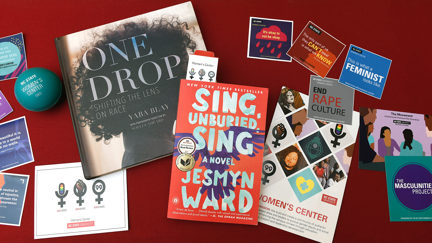 A flat lay image that includes Women's Center stickers, flyers and a copy of the book Sing, Unburied, Sing.