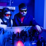 Two young adults work with lasers.