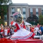 Ms. Wuf waves at NC State students as a red car drives her down Hillsborough Street.