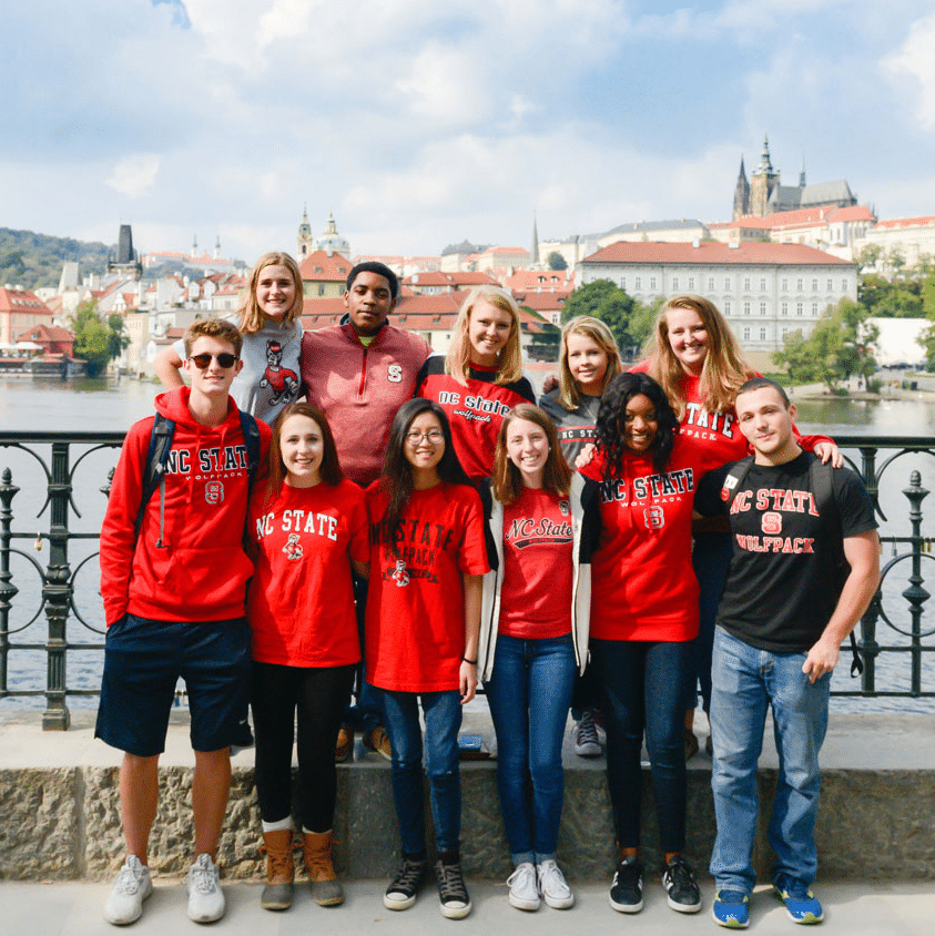 A group of students wearing red pose for a photo together on a bridge in Prague.