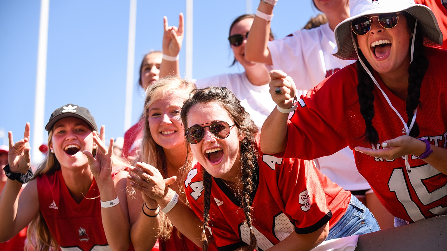 Students donning red jerseys cheer at an NCState football game.