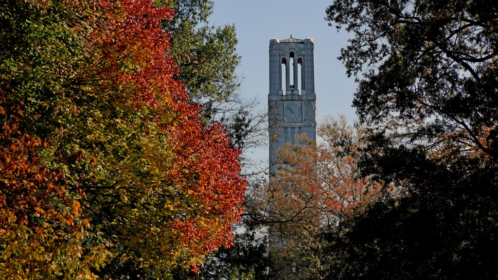 A shot of the Belltower surrounded by bright orange trees in fall.