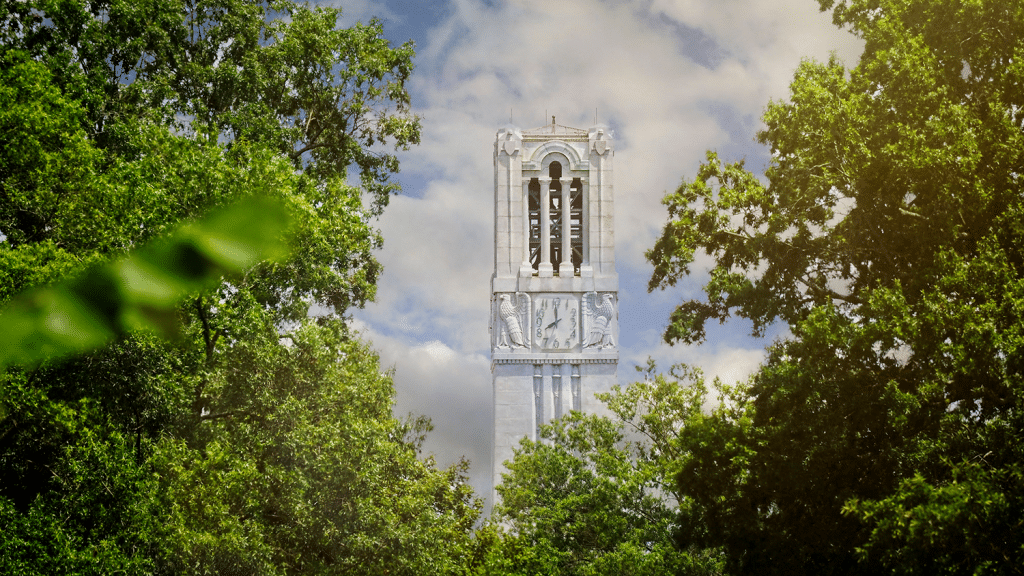 A shot of the Belltower surrounded by lush green trees in summer.