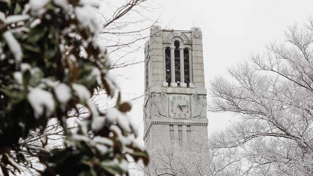 A shot of the Belltower surrounded by snow-covered trees in winter.