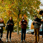 A group of students and a professor stand in a circle outside on a colorful fall day.