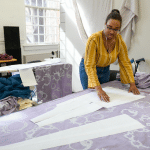 A woman in a design studio cuts pieces of fabric.